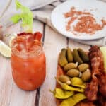 Bacon Bloody Mary with a tray of pickles and olives. In the background is the bacon salt that is used on the drink