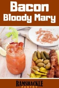 Bacon Bloody Mary with a single drink in a mason jar and several additions, such as pickles and olives, on the side