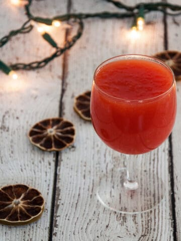 A glass of tomato juice on a wood table with dried limes and holiday lights in the background