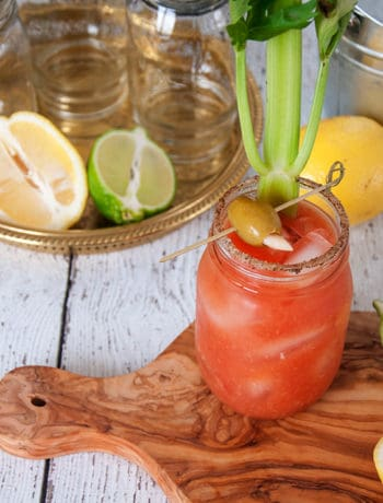 Bloody Caesar cocktail on a cutting board with various fruits and sides that go along with it