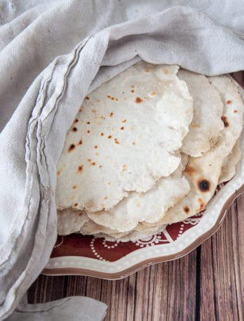Homemade flour tortillas on a white and red plate with a white towel covering