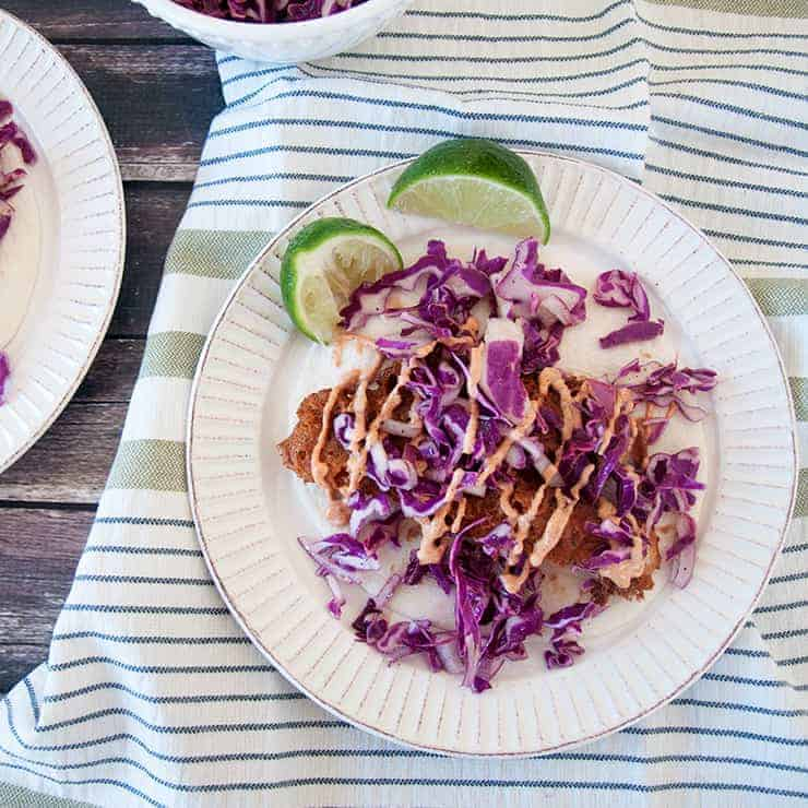 Overhead shot of the fried beer battered fish tacos with the red cabbage coleslaw and sriracha baja sauce on top.