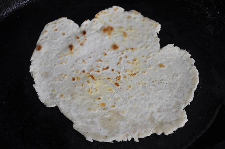 flour tortilla on a cast iron pan.