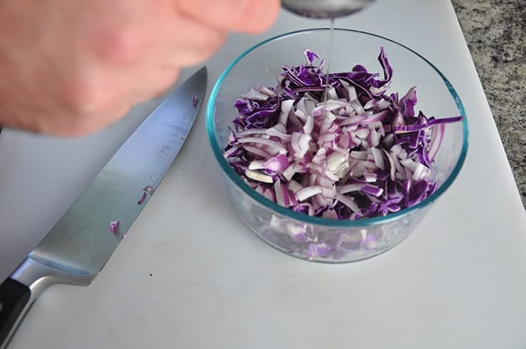 Dumping oil into red cabbage slaw