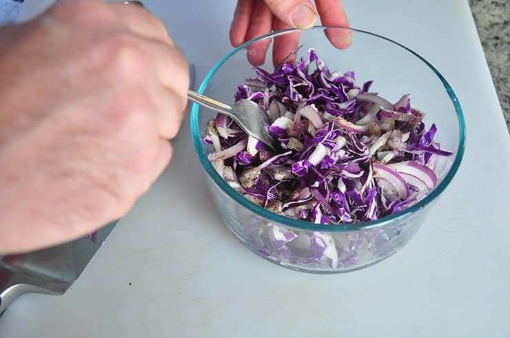 Tossing the red cabbage coleslaw for fish taco