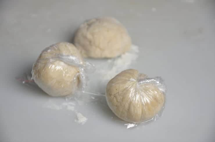 Three balls of dough individually wrapped in plastic wrap
