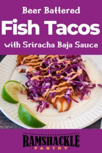 """""""Beer Battered Fish Tacos With Sriracha Baja Sauce"""" and a fish taco on a white plate with a few spent limes on the side."""