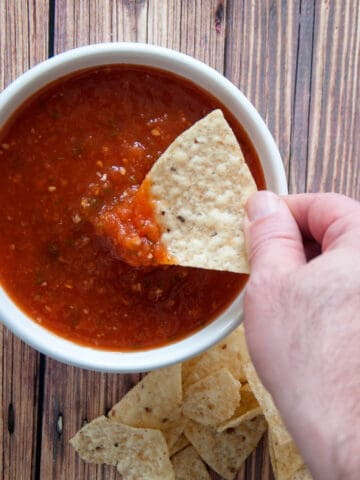 A hand dipping chips into our homemade salsa in a white bowl.