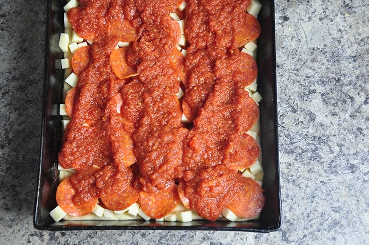 Sauce on top of pizza before cooking.