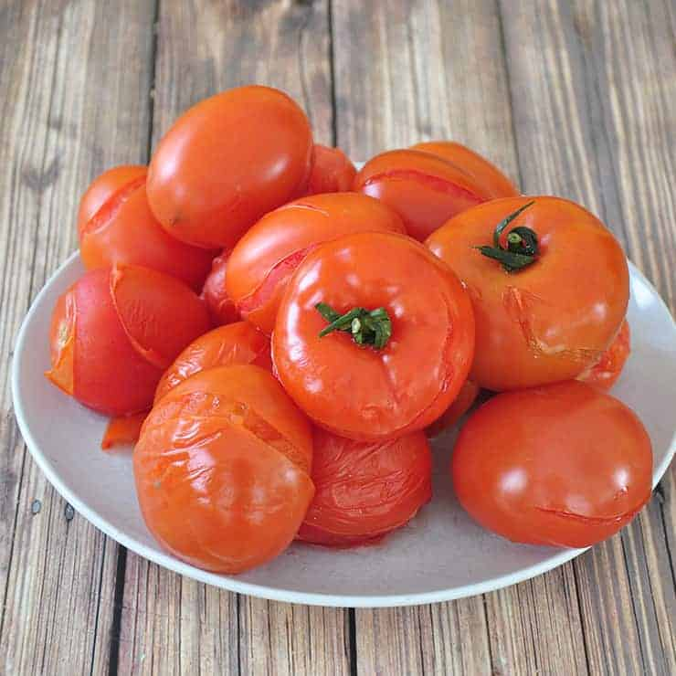 A bunch of blanched tomatoes on a white plate