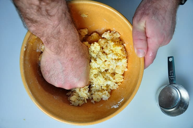 Using hand to smoosh the thawed tater tots, egg, and flour together