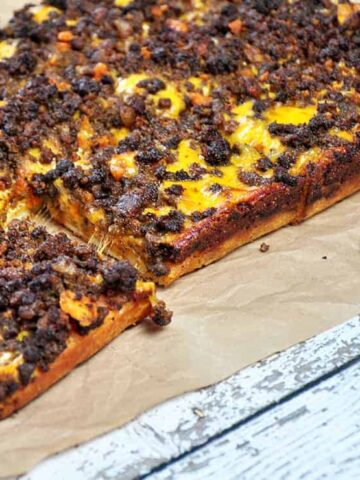 Detroit Style Coney Island pizza on a brown paper mat.