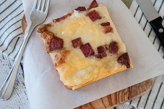 One Slice of Rueben Pizza on a parchment paper and cutting board