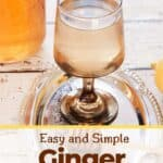 Easy and Simple Ginger Tea with one glass of our tea on a silver platter and a jar filled with honey.