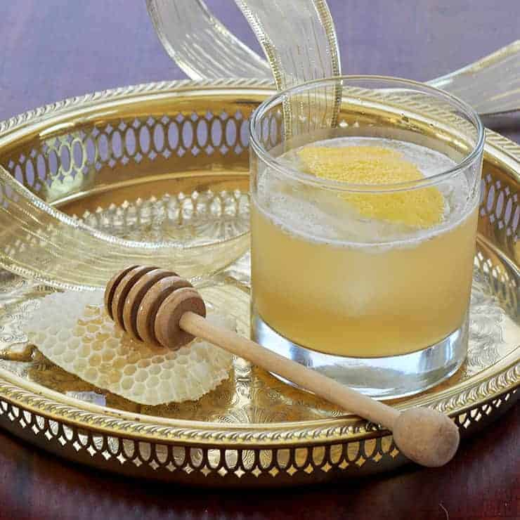Gold Rush Cocktail on a Gold Platter with honey and a honey dipper to the side
