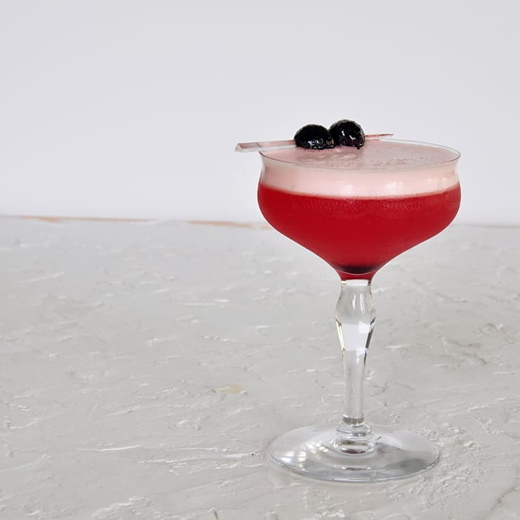 A Single Sam Ross Sour Cocktail on a white backtdrop and garnished with two maraschino cherries