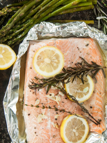 Overhead view of a tin foil grilled salmon fillet recipe, still in foil and some asparagus on the side.