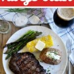 How To Grill Ribeye Steak with a steak on a plate with potatoes, corn, and asparagus.