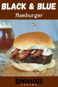 """""""Black & Blue Hamburger"""" on a cutting board with a beer in the background."""