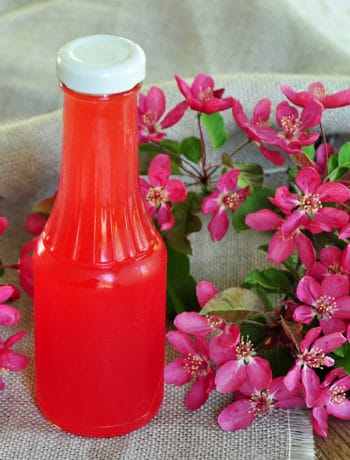 Rhubarb Syrup in a bottle on a picnic table with flowers laying around.