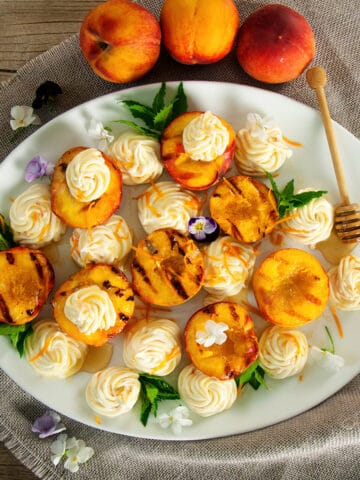 4 Grilled peaches on a big white serving platter topped with the honey whipped mascarpone cheese and mint.