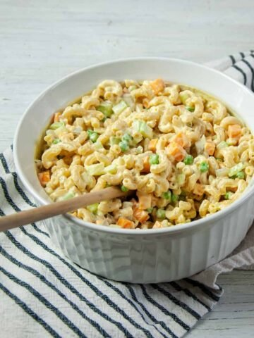 Rancharoni Macaroni in a large white dish and wooden spoon in it.