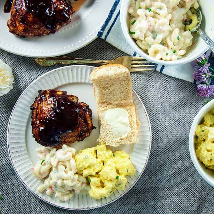 Grilled BBQ Chicken Thigh on a plate with potato salad, macaroni salad, and a Hawaiian Bun