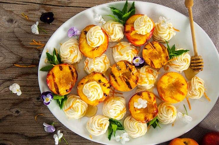 Overhead view of grilled peaches and whipped mascarpone with honey.