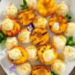 Plate of grilled peaches with mascarpone sauce on top and mint to garnish.