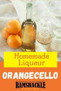 """Homemade Liqueur Orangecello"" with a bottle, two glasses, and three oranges."
