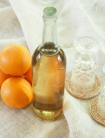 Liter bottle of Orangecello with 4 oranges and two glasses beside the bottle.