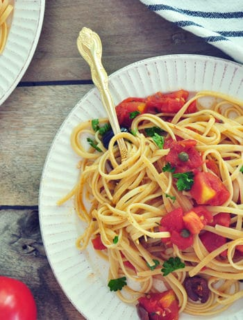 A plate of Puttanesca Sauce with Linguine on a white plate with a gold spoon. It is in a picnic table with a striped white cloth and some whole tomatoes.