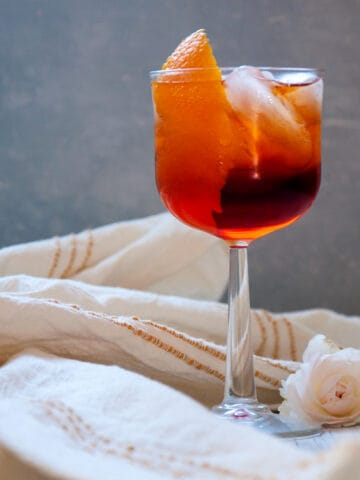 Aperol Americano Cocktail with a white napkin and flower on the table.