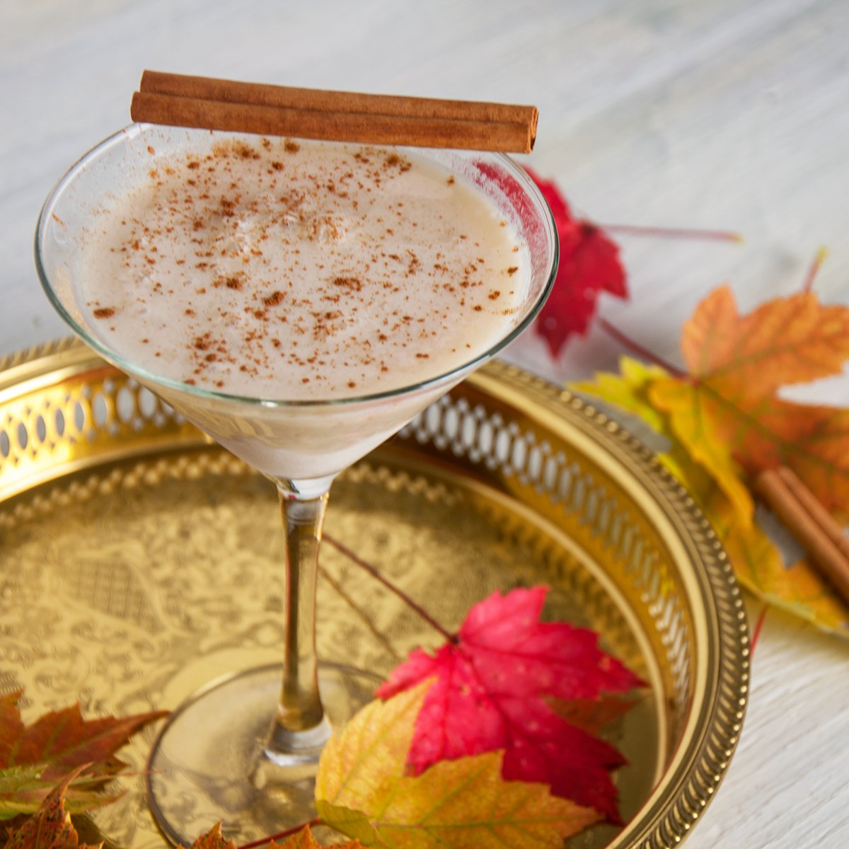 RumChataTini cider cocktail on a gold platter with Fall leaves garnishing the scene.