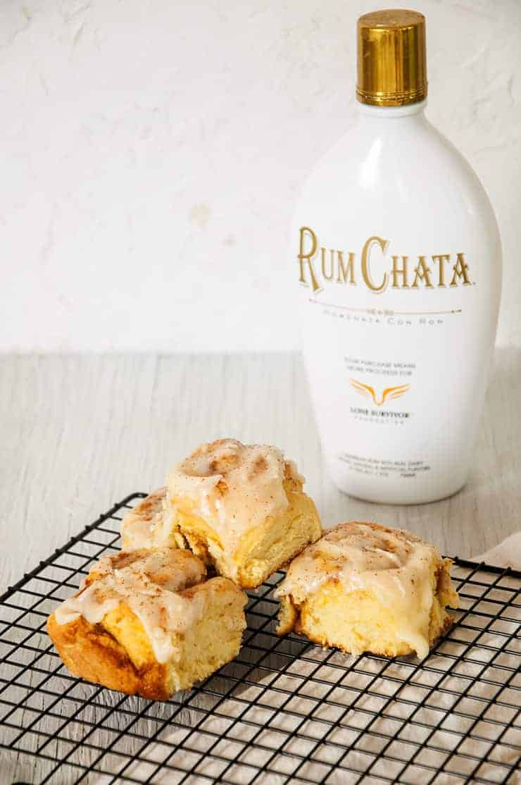 Pumpkin Cinnamon Roll Recipe with three rolls and a bottle of RumChata in background