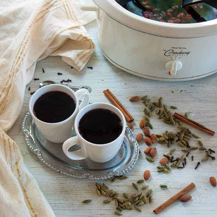 Two coffee mugs of this glogg recipe on a white sheet with spices in the background.