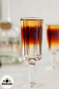 The Total Yodel Shot Recipe with one in the background and a bottle of Goldshlager