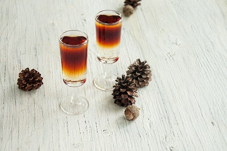 Two Total Yodel Shots on a table with pine cones in the background.