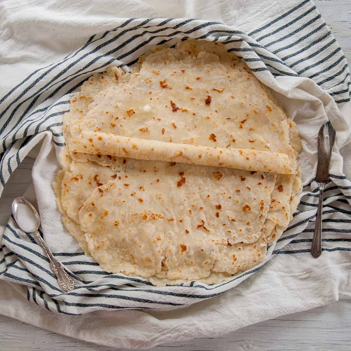 Flat lefse being rolled on a blue napkin.