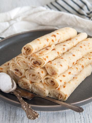 Pile of lefse from this lefse recipe on a dark plate with a knife and a spoonful of sugar.