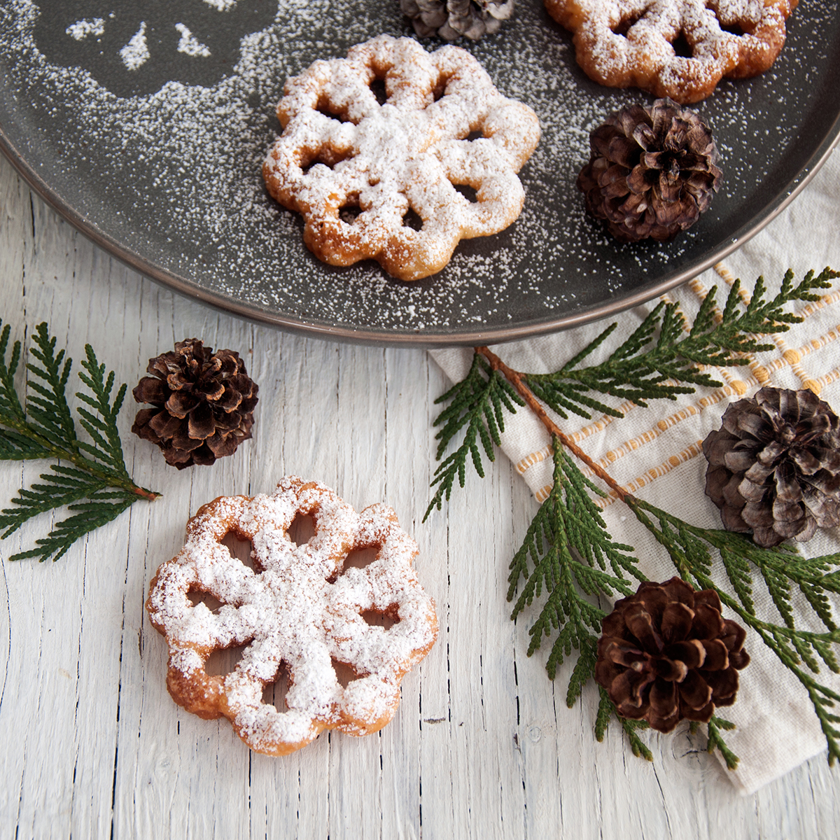 A rosette cookie on a white background with evergreen and pinecones around it and a few other ones on a plate behind it.