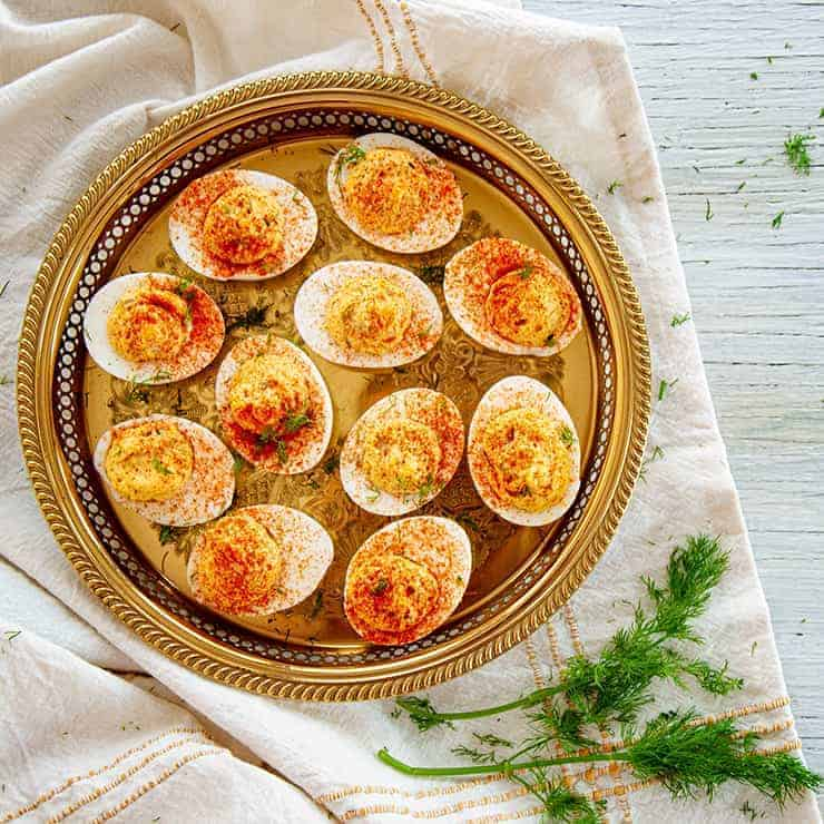 A Plate of Dill Pickle Spicy Deviled Eggs on a gold platter and dill on the side.