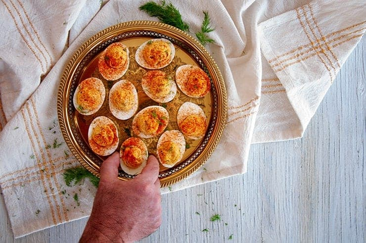 Hand Reaching onto platter of Dill Pickle Spicy Deviled Eggs and picking one up.