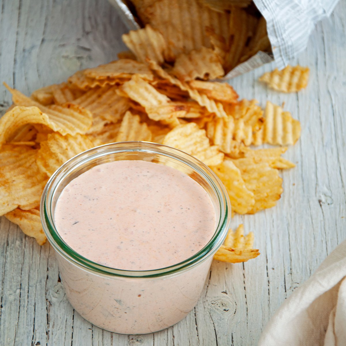 Mason jar filled with chip dip recipe on a white table with potato chips laying around it.