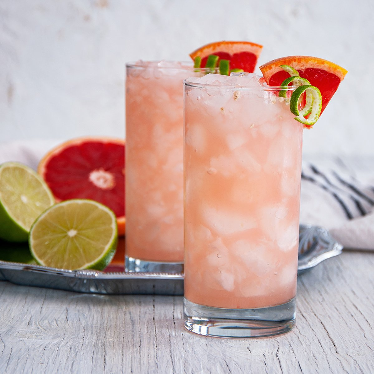 Two Paloma Cocktail recipes made - one on a white table and the other on a silver platter.