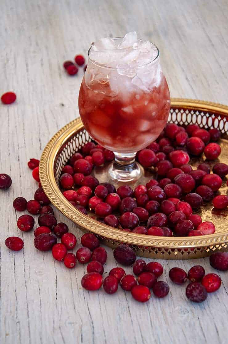 A glass of Purple Haze drink on a gold platter with cranberries all around.