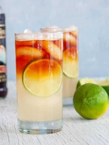Two Dark 'n Stormy cocktails on a white table with limes and a bottle of Gosling's dark rum in the background.