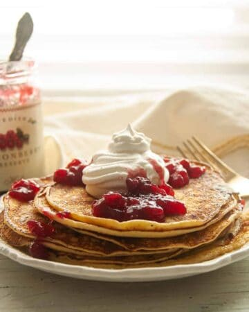 Stack of Swedish Pancakes Recipe on a white plate with Lingonberry jam, whipped cream, and powdered sugar on top.