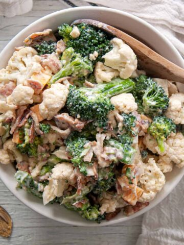 Extra Baconey Amish Broccoli Salad Recipe in a white bowl with a wooden spoon!