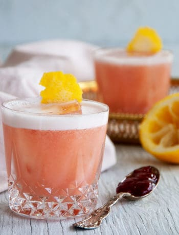 Two Strawberry Jelly and Gin Cocktails on a white table with a spoon of jelly and a juiced lemon on the side.